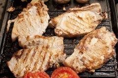 Chuletas de cerdo y tomates asados a la parrilla en una plancha Fotografía de archivo