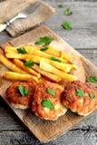Chuletas de la carne de Turquía servidas con las patatas y adornadas con perejil en un tablero de madera montante rústico primer Fotos de archivo libres de regalías