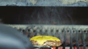 Chuletas del cheeseburger cocinadas en una parrilla de la barbacoa almacen de video
