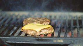 Chuletas del cheeseburger cocinadas en una parrilla de la barbacoa para el fin de semana del día de fiesta del país almacen de metraje de vídeo