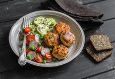 Chuletas del pollo y ensalada de las verduras frescas en la placa de cerámica en fondo de madera oscuro Imagenes de archivo