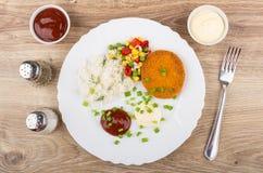 Chuletas fritas con el arroz y las verduras, salsa de tomate, mayonesa, spi Foto de archivo