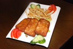 Chuletas fritas de los pescados con las patatas fritas y las verduras en la placa blanca fotos de archivo libres de regalías