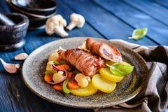 Chuletas fritas del cerdo envueltas en tocino y rellenas con la cebolla y la mostaza, adornado con la patata y la verdura cocida  Foto de archivo libre de regalías