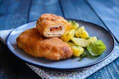 Chuletas fritas del cerdo rellenas con el tomate secado al sol y el queso del Roquefort, servidos con la patata Fotos de archivo libres de regalías