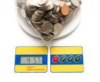 Chump Change. Business concept with use of money for presenting values of saving and spending. Depicted here with bag of coins on scale Royalty Free Stock Image