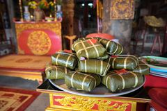 Chung cake on altar in old village communal house. Cooked square glutinous rice cake, Vietnamese lunar new year food.  Royalty Free Stock Image