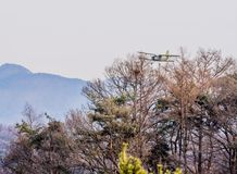 Biplane flying over mountainous region. Chungju, South Korea, February 22, 2018: ROK military biplane training aircraft flying over mountainous region on Royalty Free Stock Photos