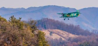 Biplane flying over mountainous region. Chungju, South Korea, February 22, 2018: ROK military biplane training aircraft flying over mountainous region on Royalty Free Stock Photo