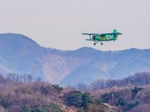 Biplane flying over mountainous region. Chungju, South Korea, February 22, 2018: ROK military biplane training aircraft flying over mountainous region on Royalty Free Stock Images
