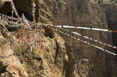 Chungsi monastery and prayer flags in Mustang. Chungsi monastery and cave in Mustang, Nepal, Himalaya. Multicolored prayer flags across the gorge. Stone wall Royalty Free Stock Photo