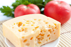 Chunk of cheese on a background of red tomatoes Stock Photos
