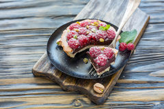 Chunk tartlets with raspberries on a silver fork. Fork with a slice of raspberry tarts on a black plate, selective focus Royalty Free Stock Images