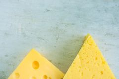 Chunk and Wedge of Alpine Creamy Appetizing Yellow Tilsit and Maasdam Cheese on Scratched Grey Metal Background. Texture. With Cracks and Holes. Minimalist stock photos