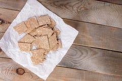 Chunkes de los biscotes curruscantes del maíz en el documento de embalaje blanco sobre viejo fondo de madera diagonal fotos de archivo