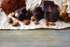 Chunks of chocolate, nuts and cocoa Stock Images