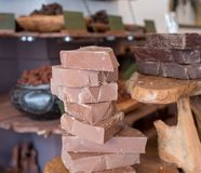 Chunks of chocolate piled up on a wooden counter in a store in Brick Lane, London, UK. stock photography