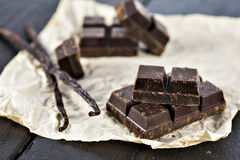 Chunks of dark chocolate bar and vanilla beans Royalty Free Stock Images