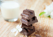 Chunks of dark chocolate in a glass of milk on the boards Royalty Free Stock Image