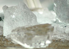 Chunks of ice on a wooden table. They are irregular in shape, with a shallow depth of field Stock Image