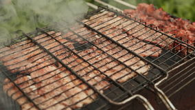 Chunks of meat fried metal grid outdoors stock video