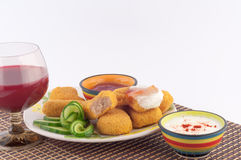 Chunks of Meat. Meat nuggets with sauce, cucumber and glass of red wine on a white background stock image