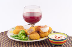 Chunks of meat. Meat nuggets with sauce, cucumber and glass of red wine on a white background stock photo