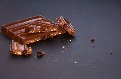 Chunks of milk chocolate with crushed hazelnuts and raisins with alcohol on black background. Confectionery degustation. stock images