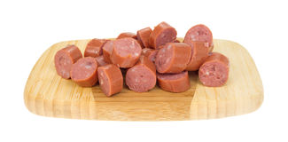 Chunks of smoked sausage on a wood cutting board Stock Photos