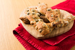 Chunky Italian Olive Breadsticks. On a wooden Heart Shaped Chopping Board Stock Image