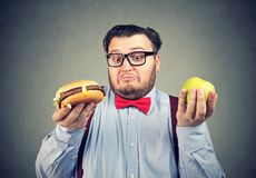 Chunky man making choice in diet royalty free stock image