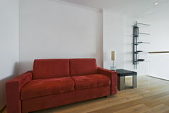 Chunky sofa. Large chunky sofa in red with a small side table and shelves Royalty Free Stock Photo