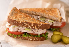 Chunky Tuna Salad Sandwich. A delicious flaked white tuna salad sandwich with tomato, lettuce, mayonnaise, and pickles Stock Image