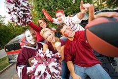 Chupar rueda: Grupo de estudiantes universitarios emocionados para el partido de fútbol Foto de archivo libre de regalías