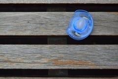 Chupeta azul em um banco imagens de stock
