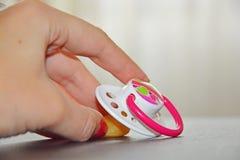 Chupeta do bebê e mão das mães Foto de Stock Royalty Free