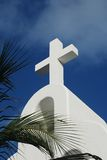 Church. White sandstone church with cross over blue sky, palm trees Royalty Free Stock Photo