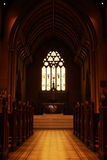 Church aisle. Low angle view of a church aisle with pews and stained glass window stock images