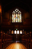 Church aisle. Low angle view of a church aisle with pews and stained glass window royalty free stock image