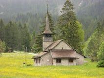 Church in an alpine meadow near Kandersteg, Switzerland. Church in an alpine meadow with wild flowers in front of a forest near Kandersteg, Switzerland royalty free stock image