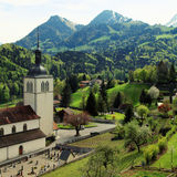 Church and Alps mountains, Gruyeres, Switzerland Stock Images