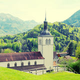 Church and Alps mountains, Gruyeres, Switzerland Royalty Free Stock Images