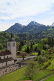 Church and Alps mountains, Gruyeres, Switzerland Stock Photography