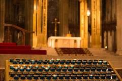 Church alter with candles lit in foreground. Candles at the church alter Stock Photo