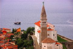 Church and angel overlooking the sea. An old venetian church overlooks an old town and the sea, as a traditional adriatic ship with stepped mast sails close to stock photo