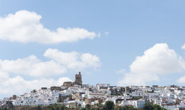 Church of Arcos de la Frontera. Blue sky and white clouds on the Church of Arcos de la Frontera, surrounded by white houses Stock Image