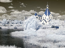 Church ashore lake. Temple of All Saints in earth Russian. Infra Stock Photography