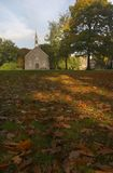 Church with Autumn Leaves. Small church in Arnhem, The Netherlands. On the foreground a lot of autumn leaves to symbolize grief and mourning Stock Photos