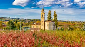 Church in autumn orchards. Church among orchards in the fall in the hills Royalty Free Stock Image