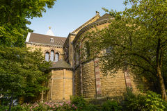 Church back facade surrounded by trees Stock Images